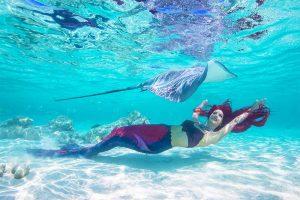 Unterwassermodel Mermaid Kat spielt mit einem Rochen in Tahiti